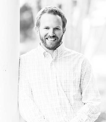 A black and white photo of our dental implant specialist Dr. Zachariah Lea Crawford smiling standing up while wearing a plaid shirt and leaning against a wall