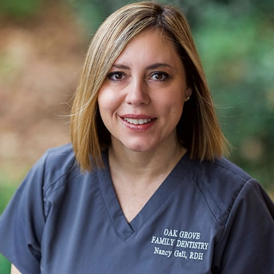 Nancy, a member of our dental hygiene team, smiling in her uniform