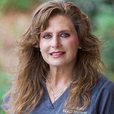 Our dental hygienist Renee, wearing her dental uniform and smiling